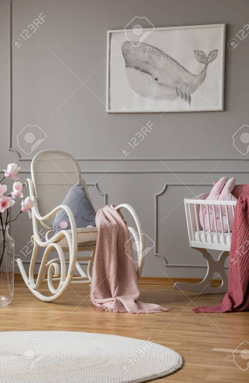 Blue pillow and paste pink blanket on white rocking chair in..