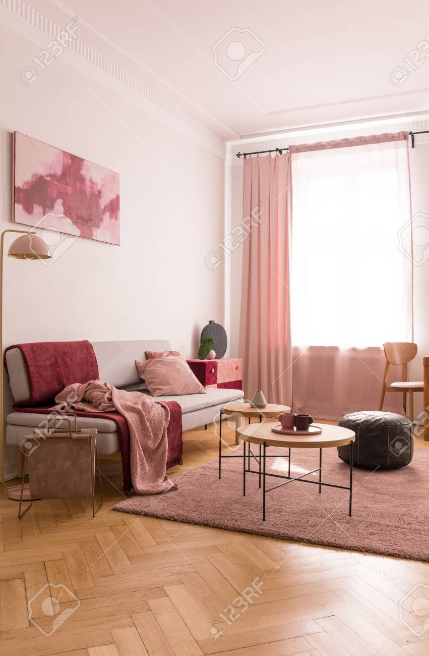 Coffee tables and old school pouf on pastel pink carpet in elegant..