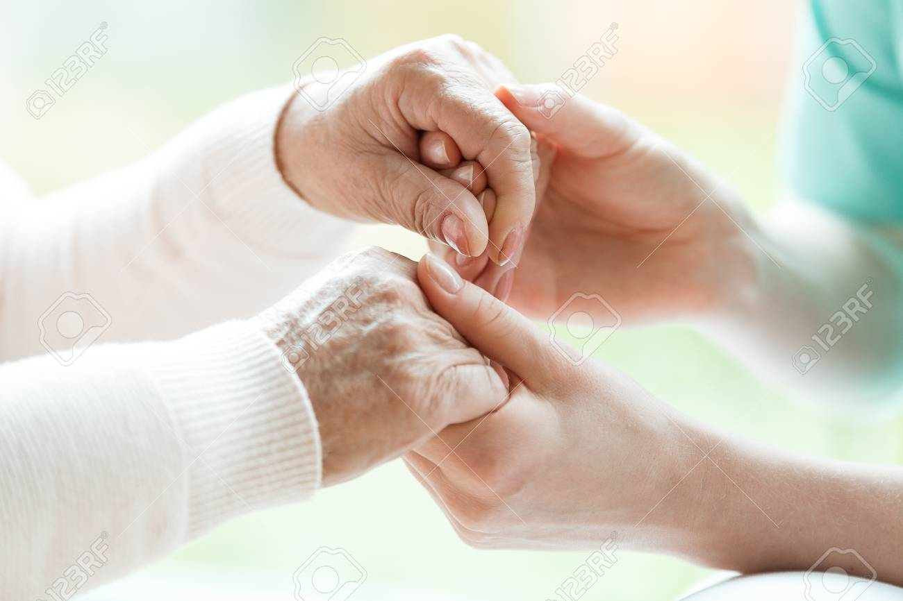 Closeup of the hands of a young woman holding hands of an elderly lady - 113820651