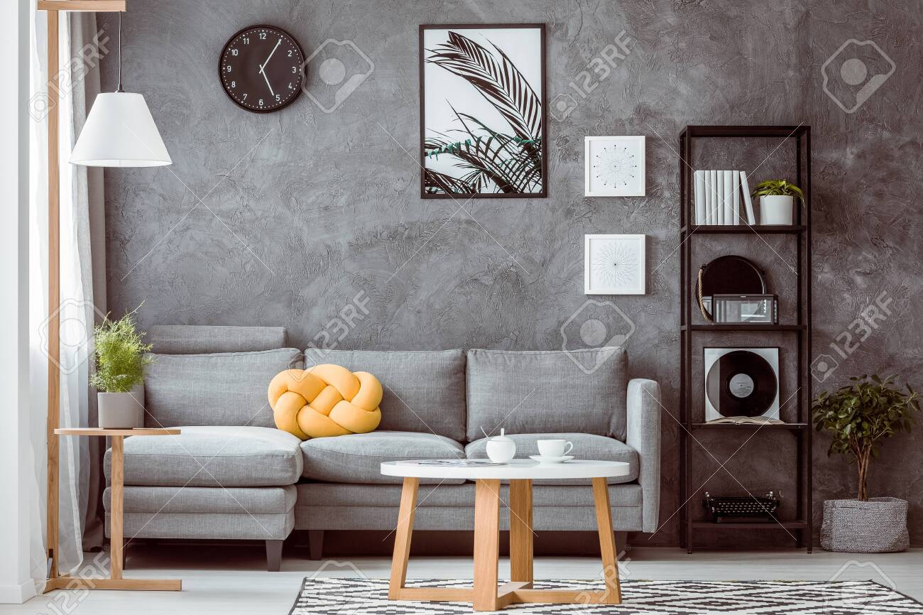 Grey concrete wall in modern living room with industrial black metal bookshelf next to comfortable sofa with yellow knot pillow - 113820659