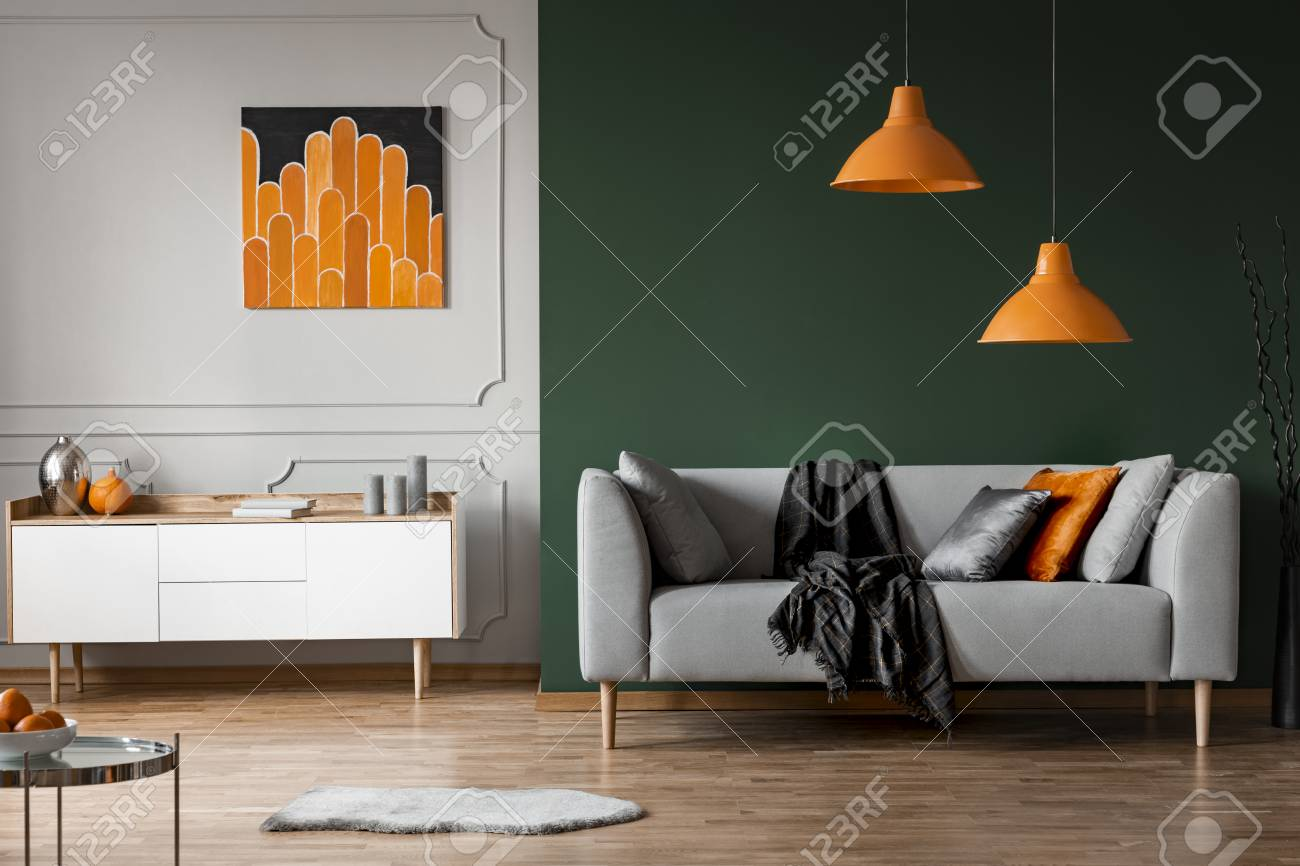 Orange lamps above grey couch in black living room interior with..