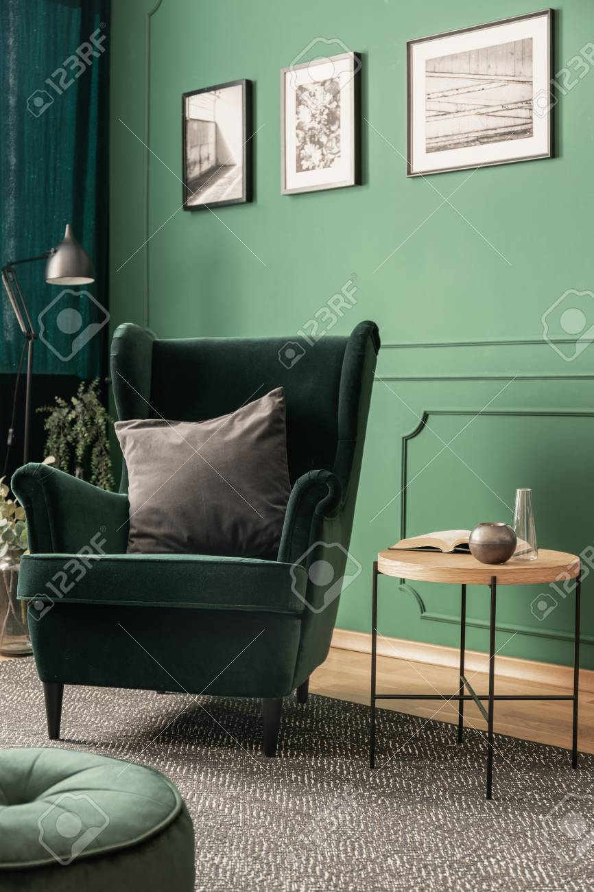 Grey pillow on emerald green armchair in green living room interior..