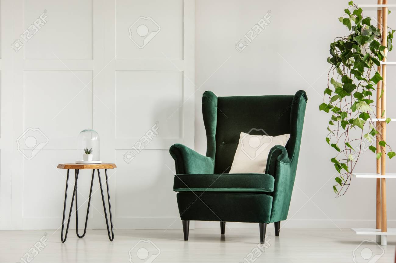 photo white pillow on emerald green armchair in contemporary living room interior with wooden coffee table