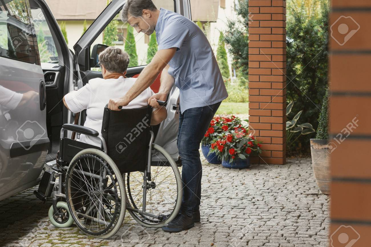 Helpful male nurse with senior lady on wheelchair helping her get in to the car - 114496875