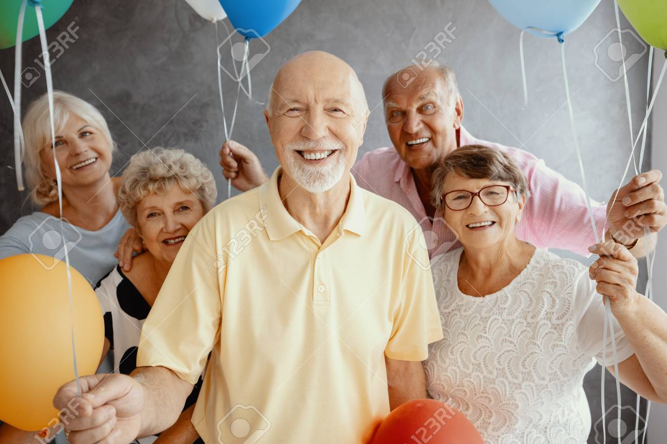 Smiling elderly people with balloons having fun during friend's birthday - 114915571