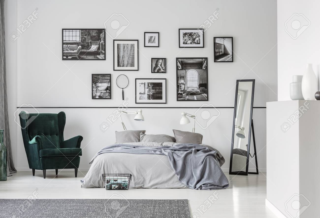 Grey bed between armchair and mirror in bedroom interior with gallery and lamps. Real photo - 115417295