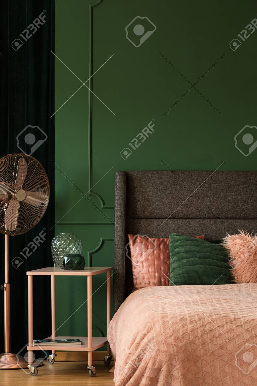 Pastel pink accents in emerald green bedroom interior with king..