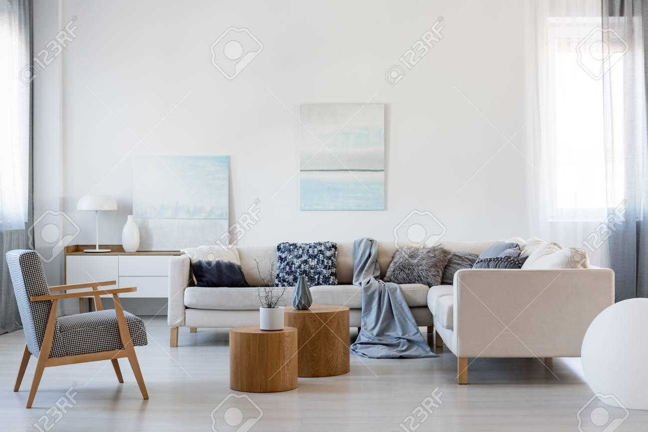 Elegant living room interior with corner sofa and retro armchair - 116649201