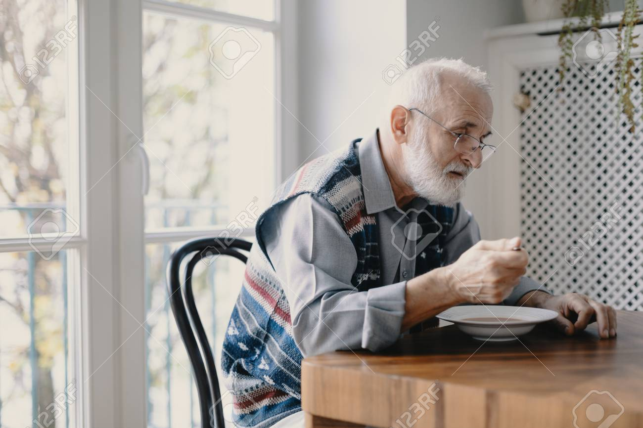 Senior grandfather with grey hair and beard sitting alone in the kitchen eating breakfast - 117919519
