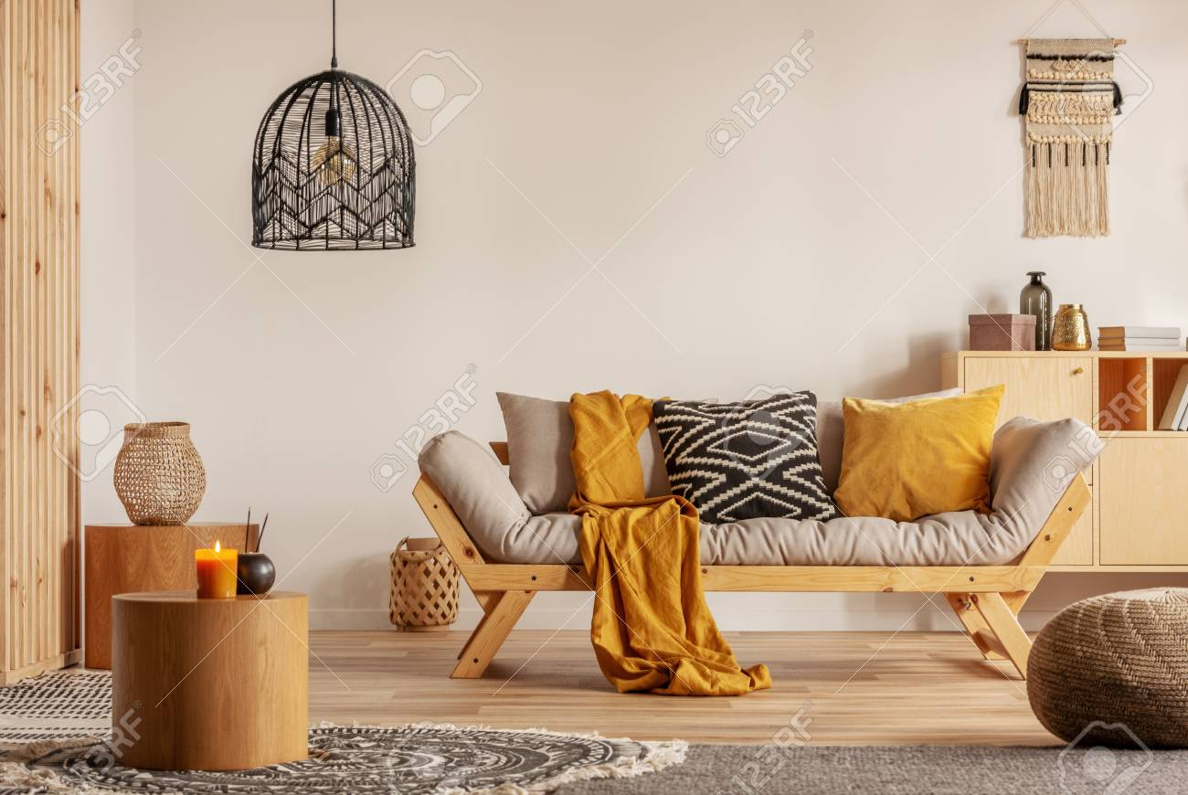 Scandinavian sofa with pillows and dark yellow blanket in bright living room interior with black chandelier - 118480869