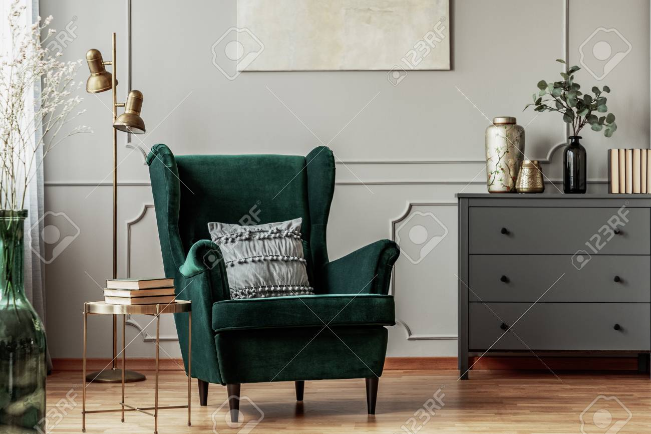 photo emerald green armchair with pillow next to grey wooden mode in dark living room interior