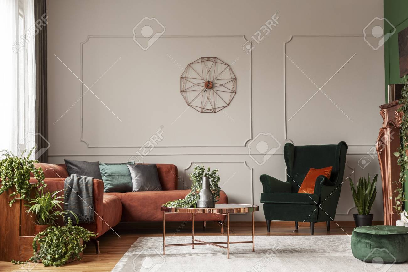 Velvet emerald green armchair with orange pillow next to corner sofa and coffee table - 119584490