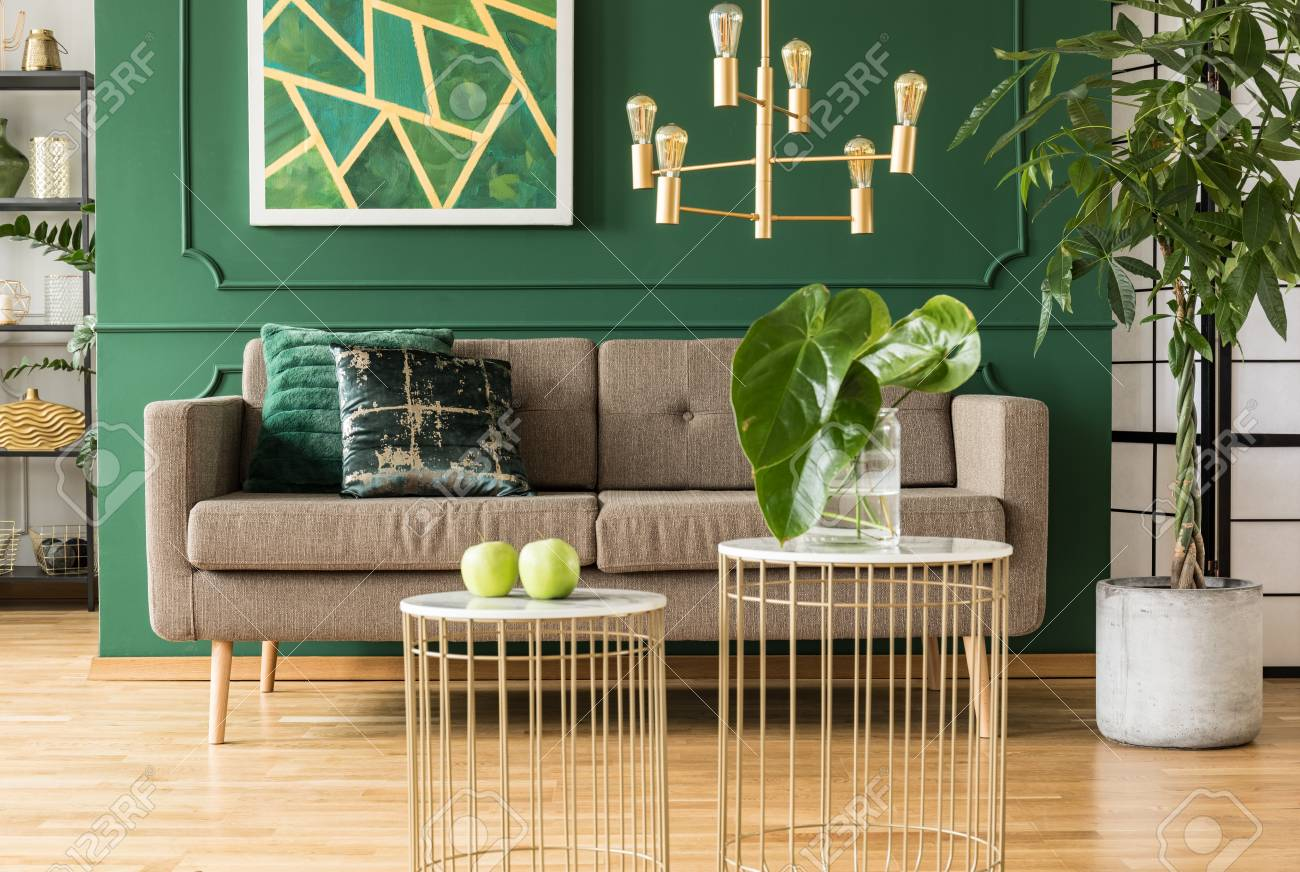 Elegant green and gold living room with comfortable brown sofa,..