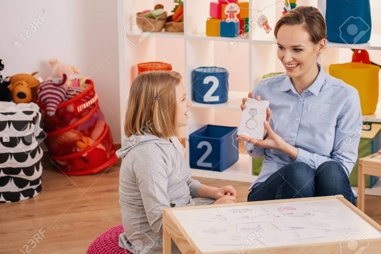 Smiling therapist showing picture of ring during meeting with autistic girl - 120835028