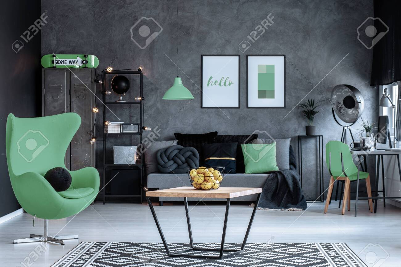 Green armchair next to wooden table in dark living room interior with posters above couch. Real photo - 121161471
