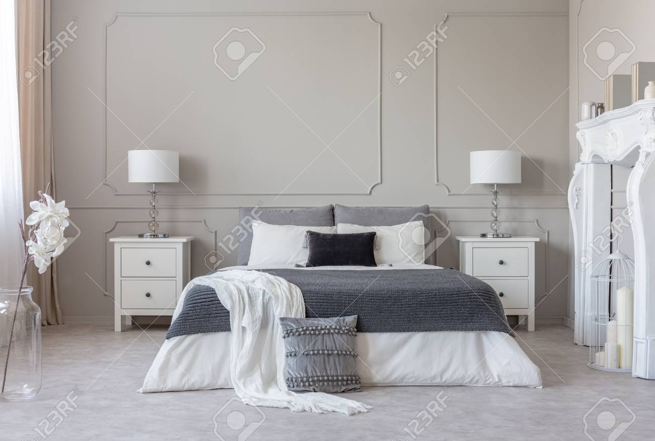 King Size Bed With Grey And White Sheets Between Two Wooden Bedside