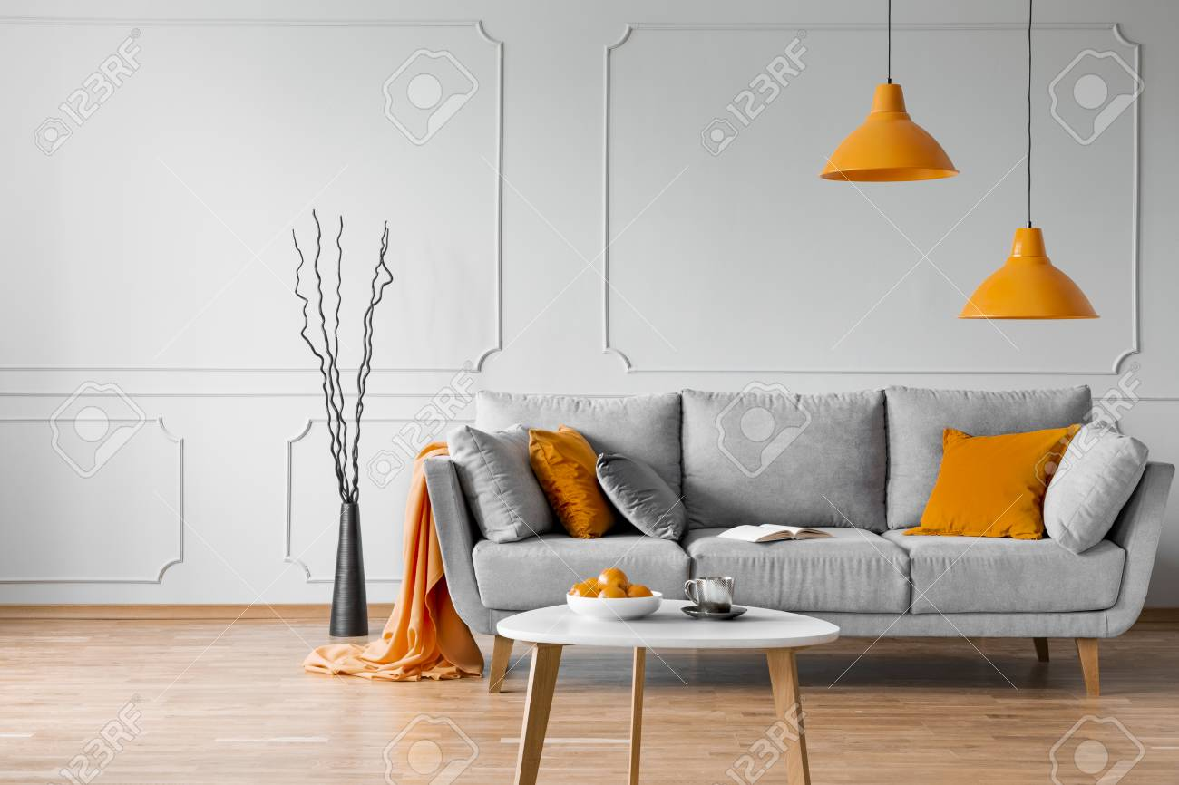 Real photo of simple living room interior with orange lamps, pillows and grey sofa - 121161631