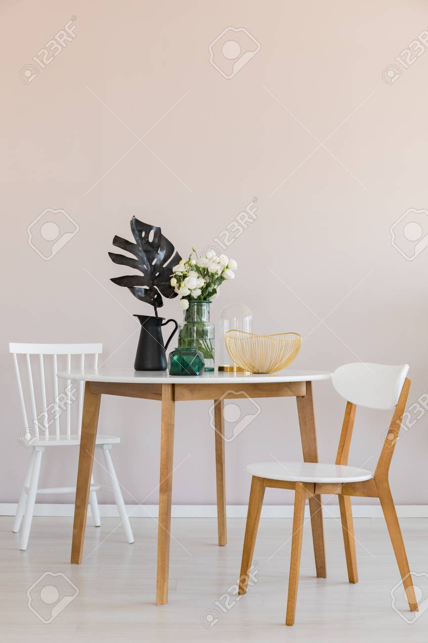 Stylish dining room with round table and elegant chairs, copy space on the empty wall - 121162076