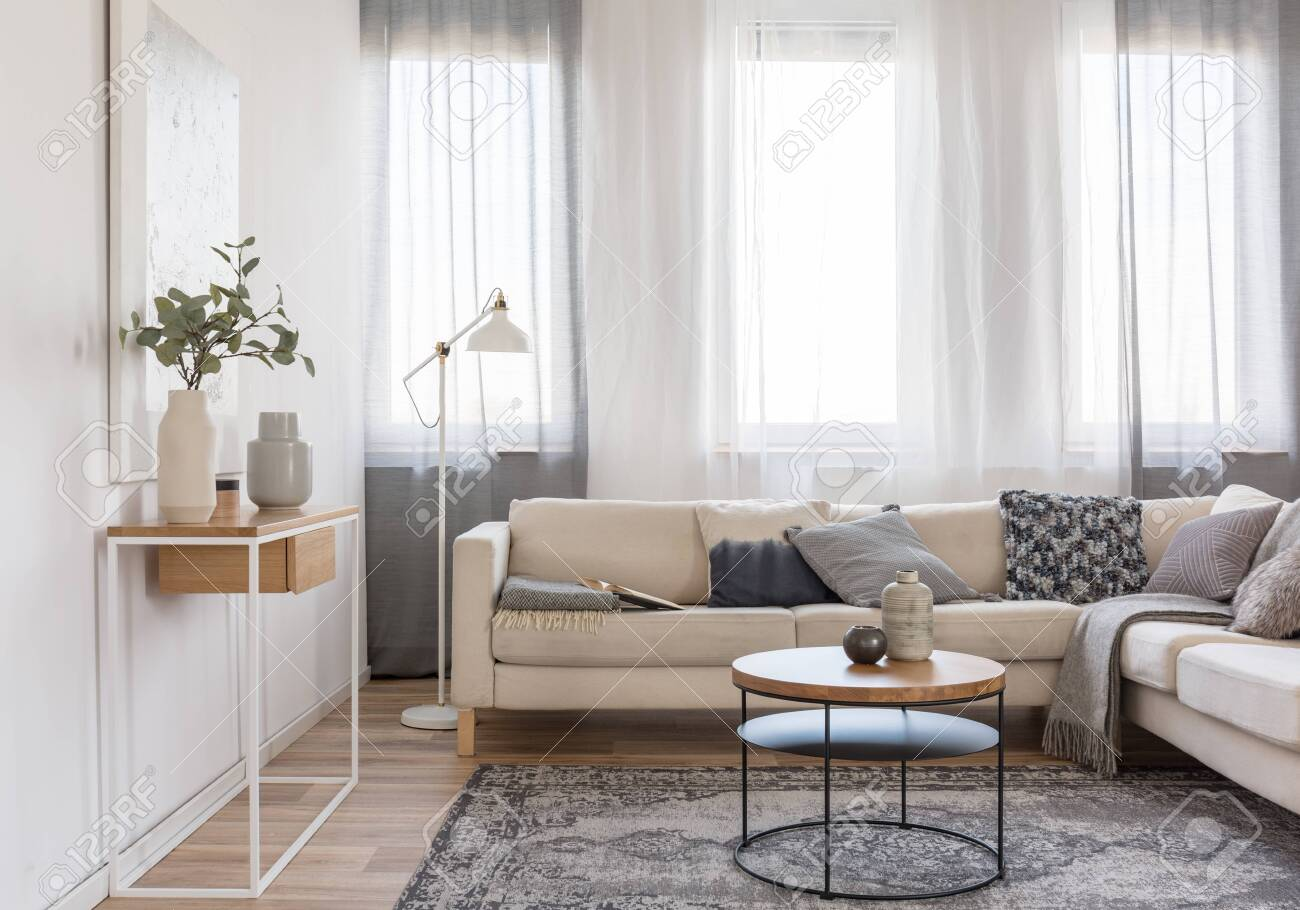 Round Coffee Table In Front Of Beige Sofa With Pillows In Bright
