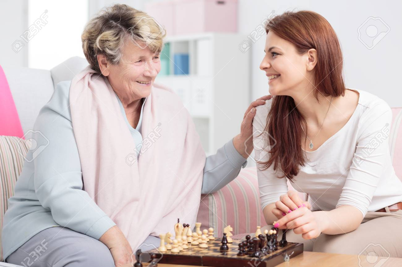 Happy granddaughter playing chess with her grandmother in senior care center - 121764289