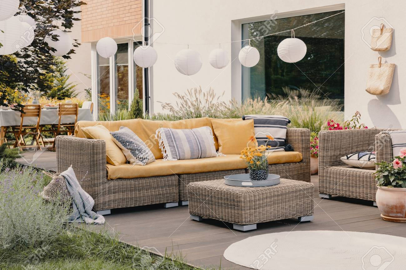 Real photo of a rattan garden furniture set with lamps and table in the background - 122007191