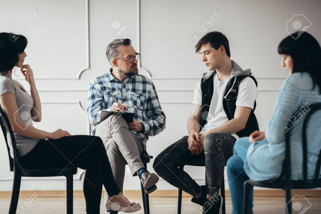 Group therapy session with psychologist and depressed man and woman - 122007889