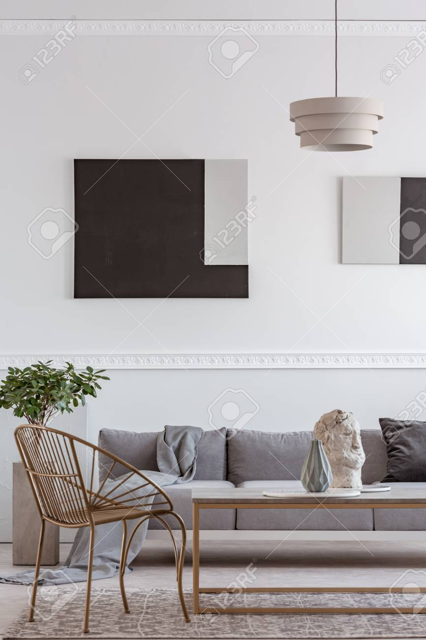 Stylish golden chair next to coffee table with vase in front of grey couch - 123114416
