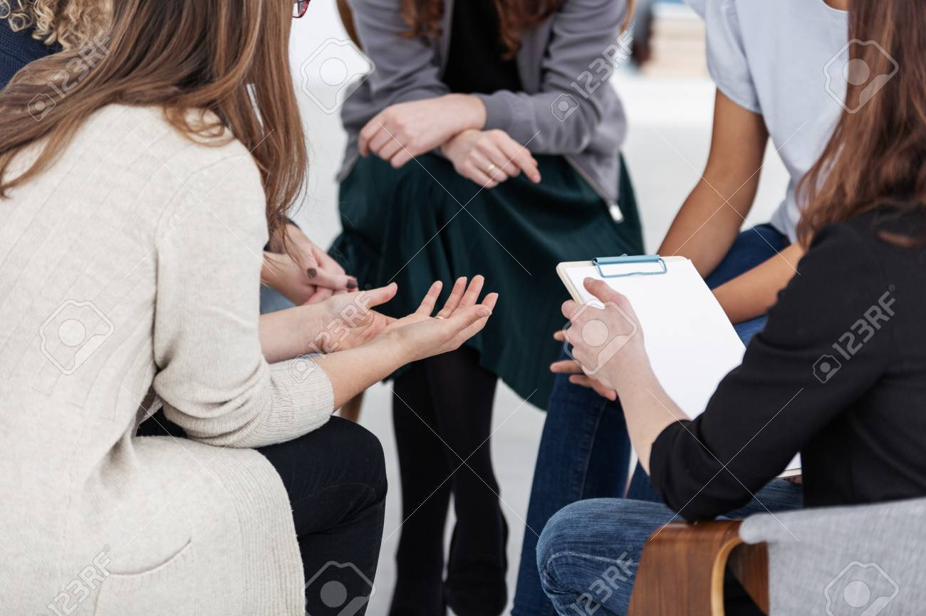 Anonymous women sitting in circle during group meeting - 123114762