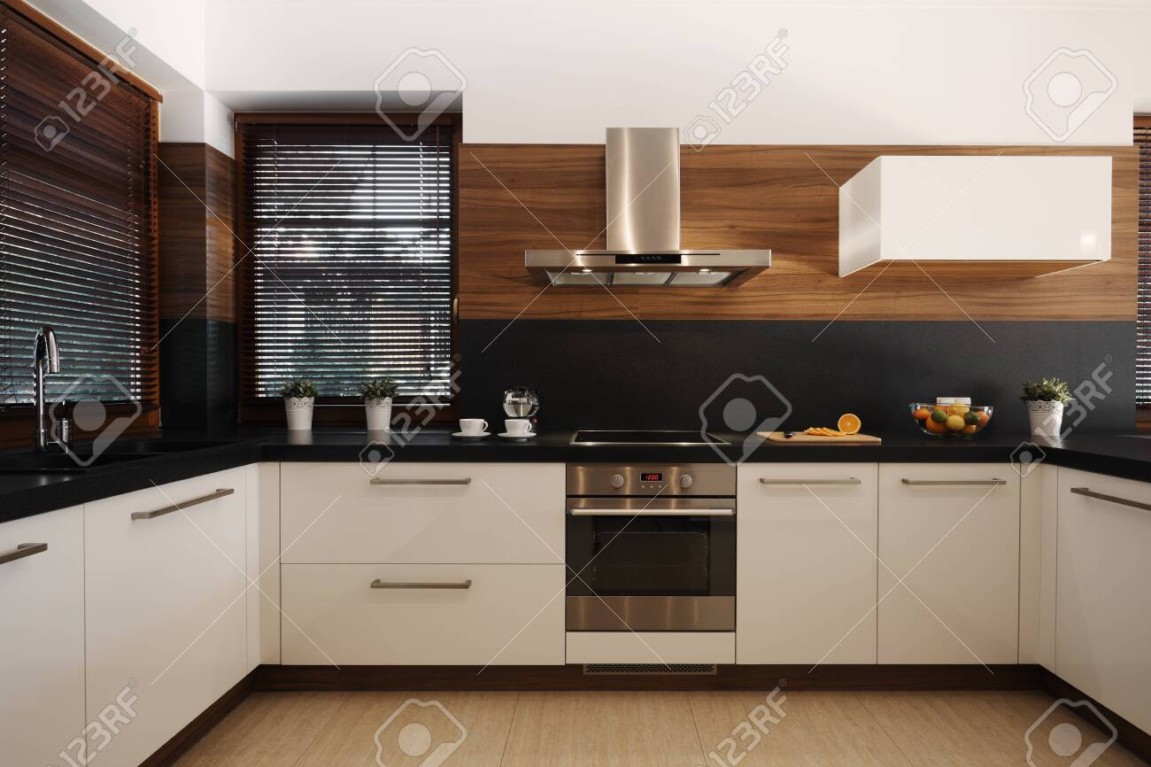Elegant white and black kitchen with wooden accents and silver oven and sink - 124428544