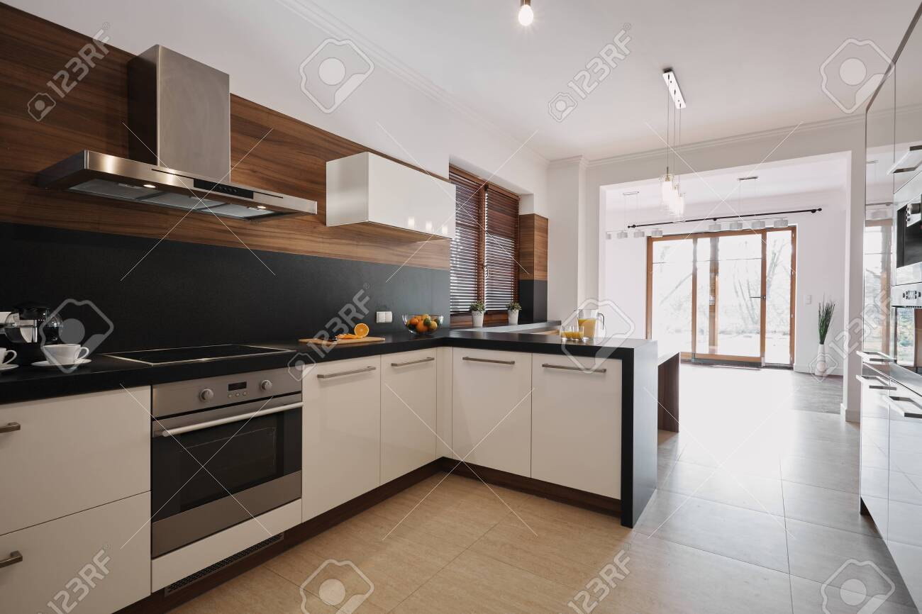 Elegant white and black kitchen with wooden accents and open space empty living room interior with floor to ceiling windows - 124428545