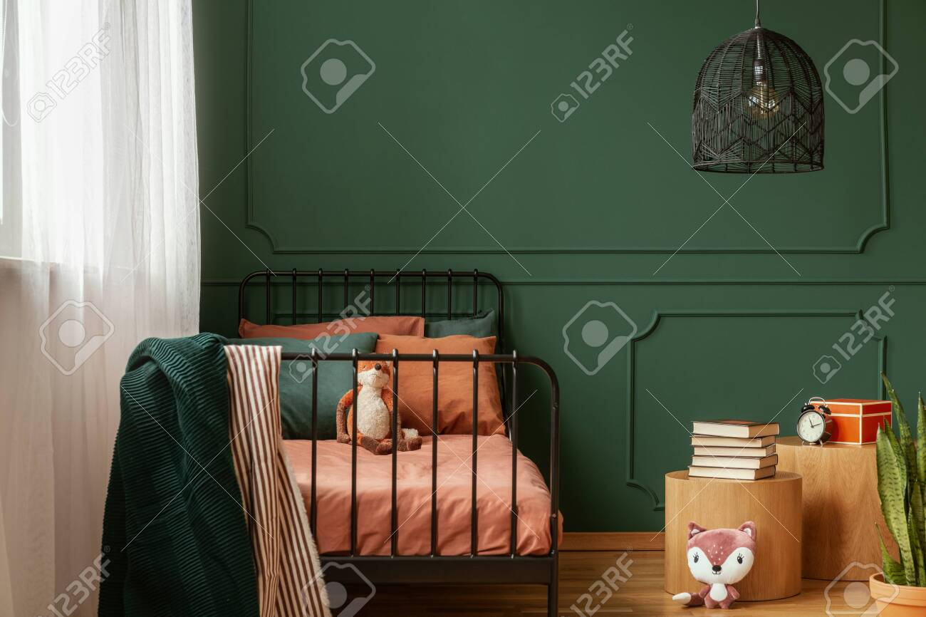 Real photo of a cute, green and orange bedroom interior for a..