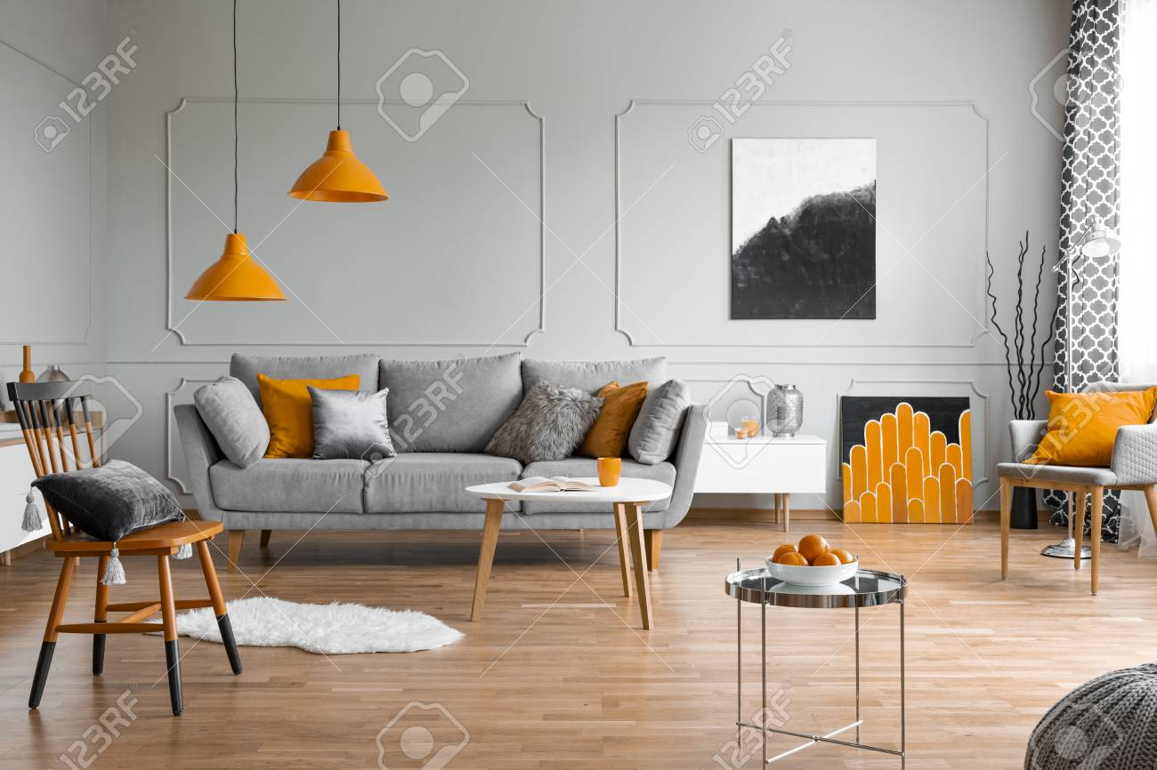 Orange accents in a grey living room interior