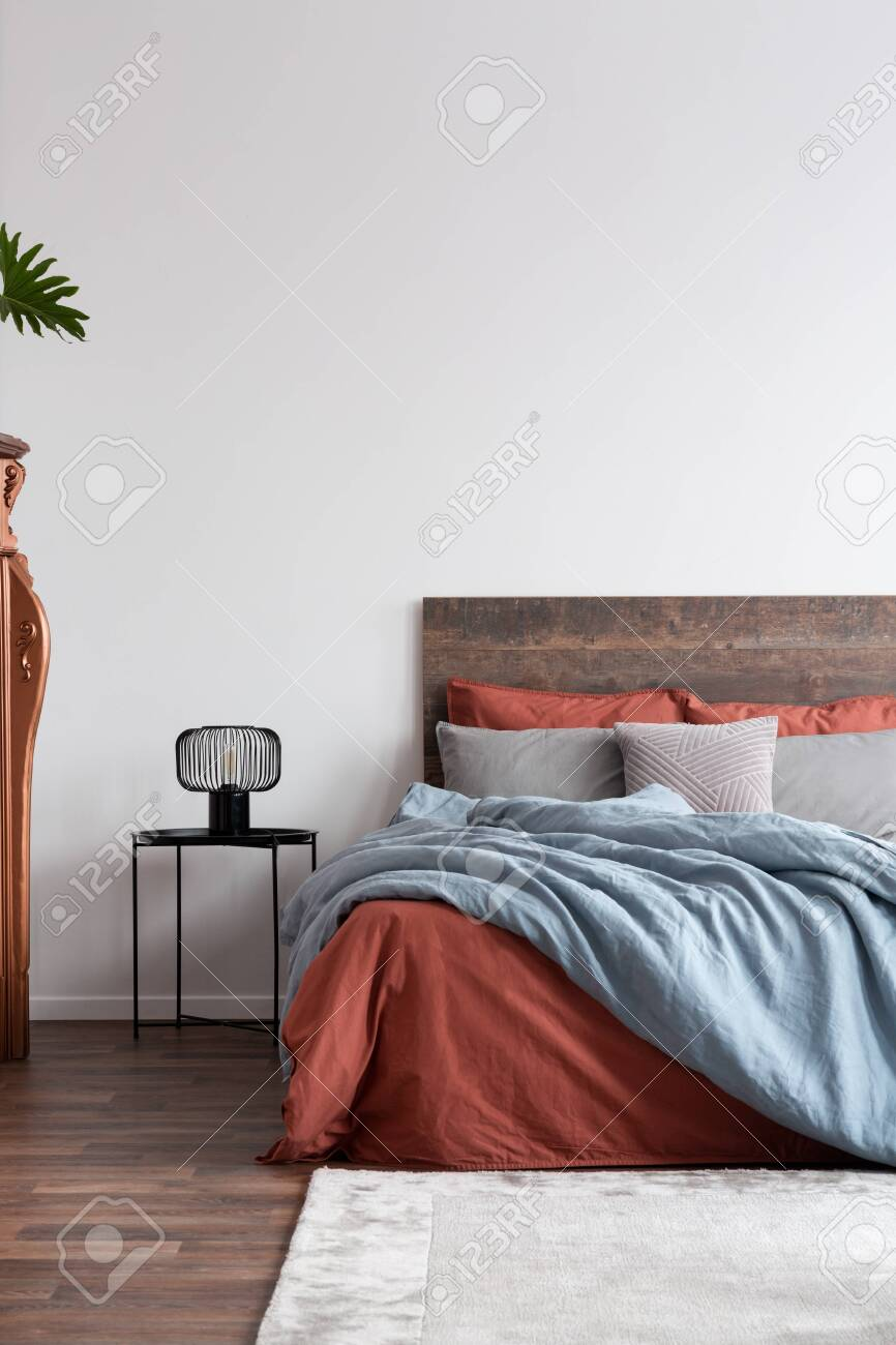 Vertical capture of a contemporary white bedroom with coral and..