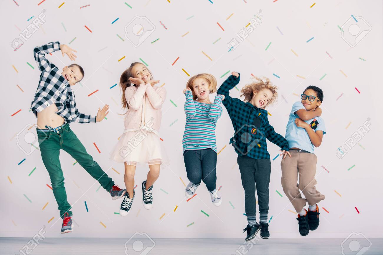 Girls And Boys Having Fun While Jumping Against Colorful Wallpaper