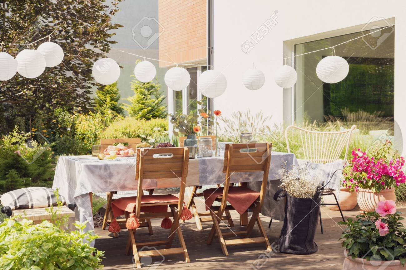 White lamps above table and wooden chairs on the terrace with flowers next to house - 124577491