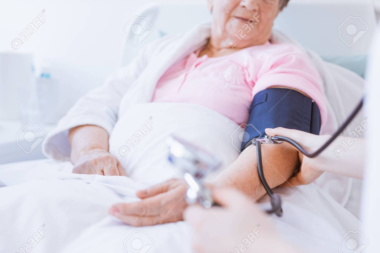 Senior woman with blood pressure monitor on her arm and young intern at hospital - 124577504
