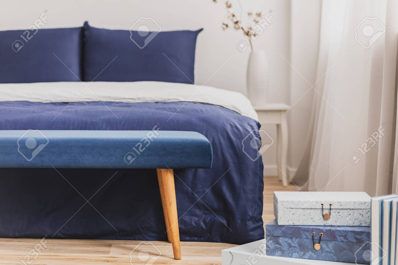 Simple navy blue and white bedroom interior with cozy bed with..