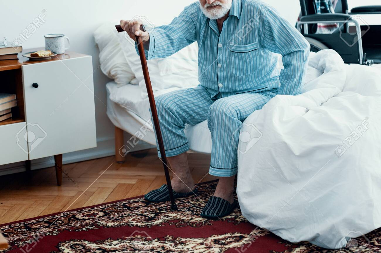 Old sick man with grey beard and hair wearing blue pajamas and sitting on bed at home - 125536457