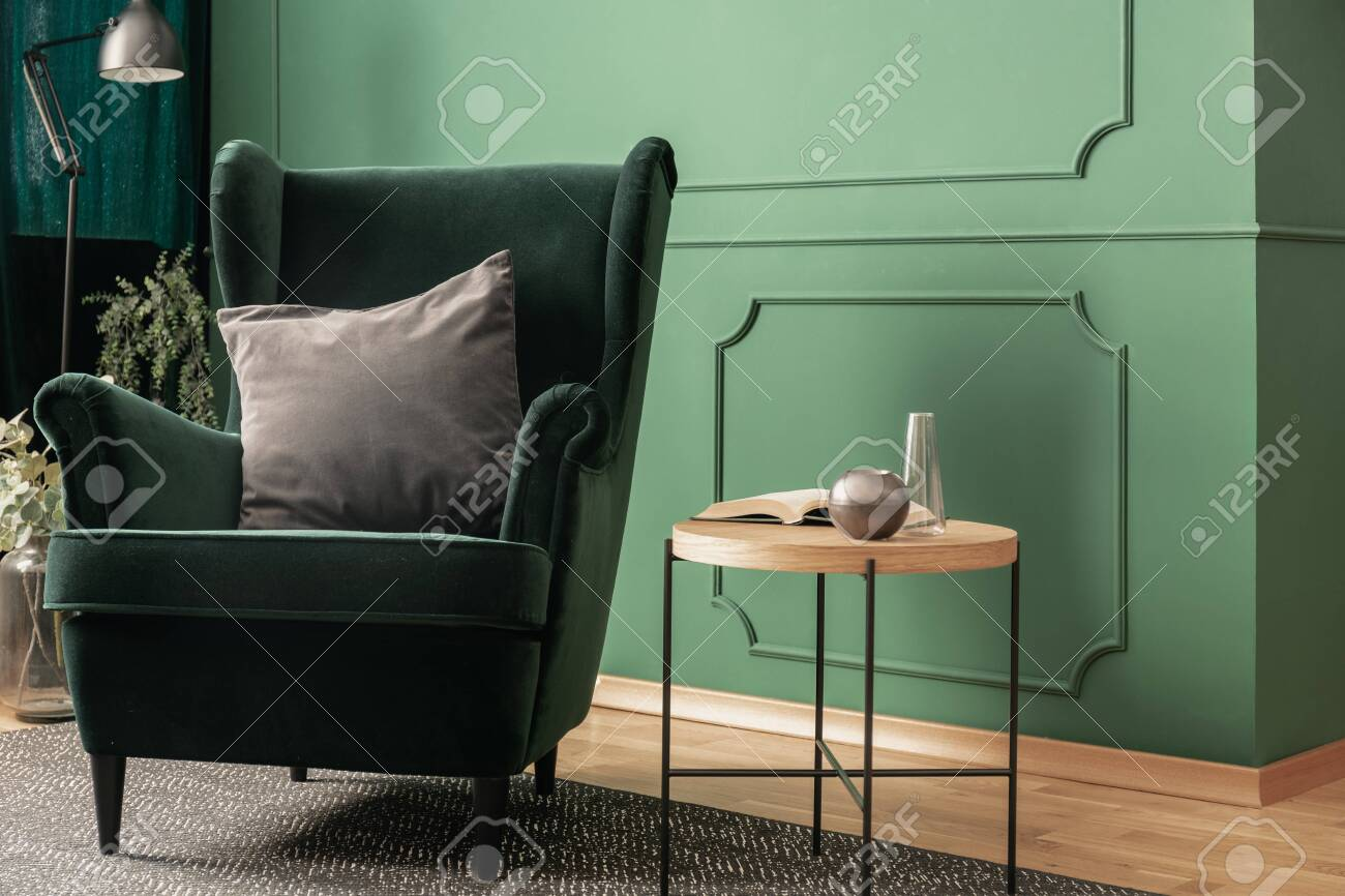 photo close up of a green velvet armchair with a gray cushion standing next to a wooden coffee table in a