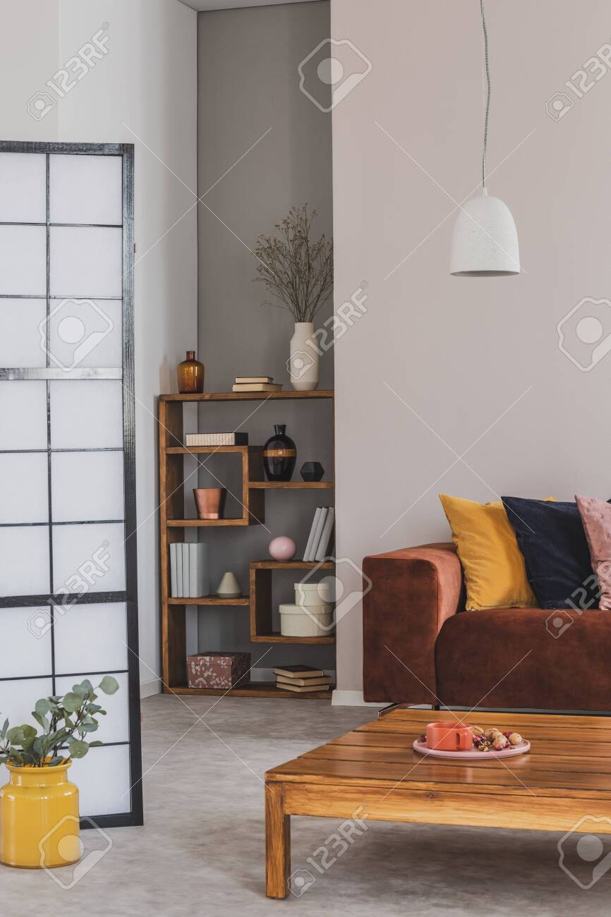 Yellow Black And Pastel Pink Pillow On Brown Couch In Grey Living