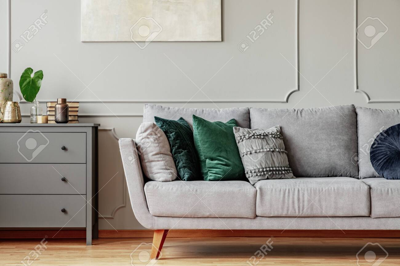 Pillows on long comfortable living room couch in grey scandinavian..