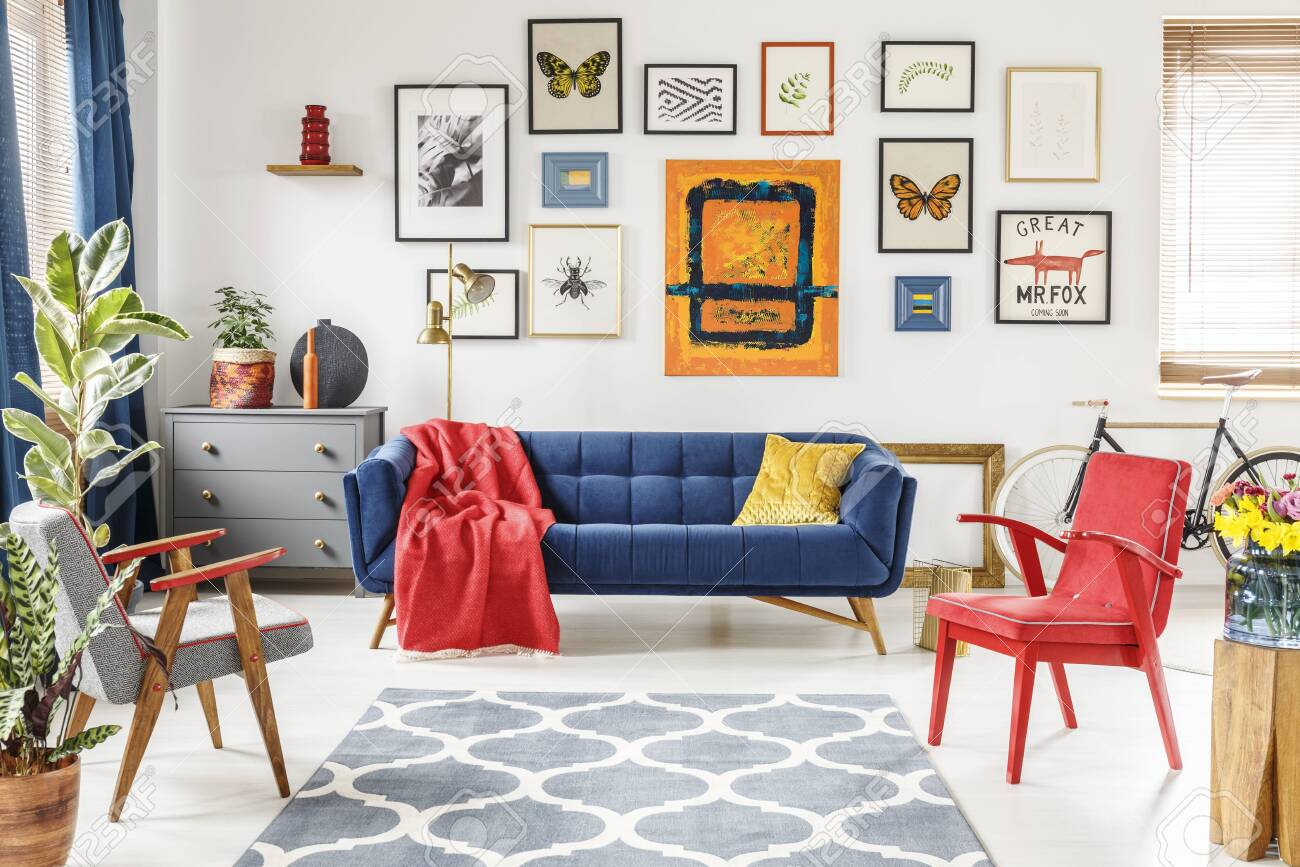 Patterned carpet in colorful living room interior with red armchair..