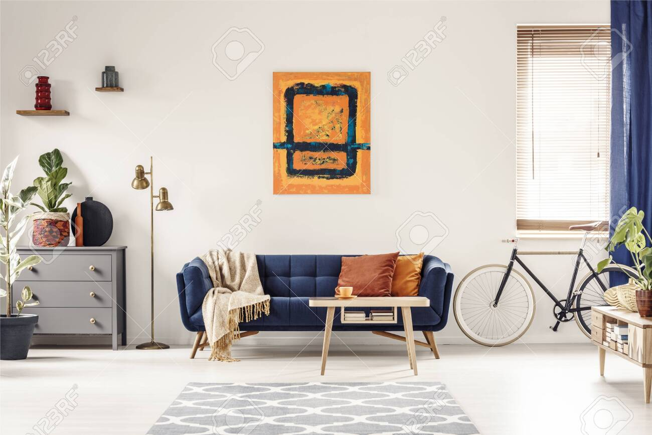 Yellow and blue painting hanging on white wall in bright living room interior with grey cupboard, gold lamp, sofa with blanket and pillows, and bike standing under window with blinds - 128629958