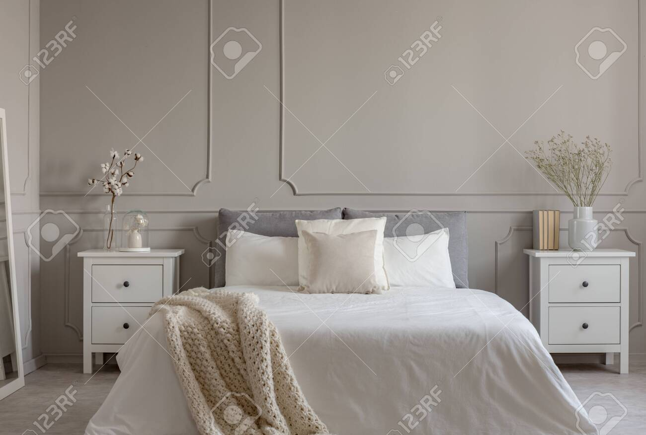 Flowers on white wooden nightstand table in luxury bedroom interior..