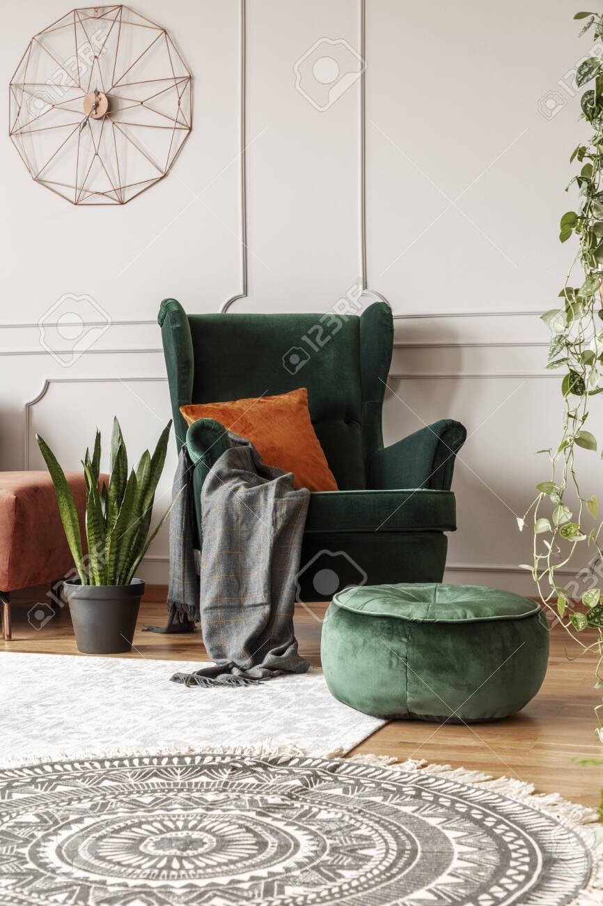 Comfortable emerald green armchair with orange pillow in fashionable..