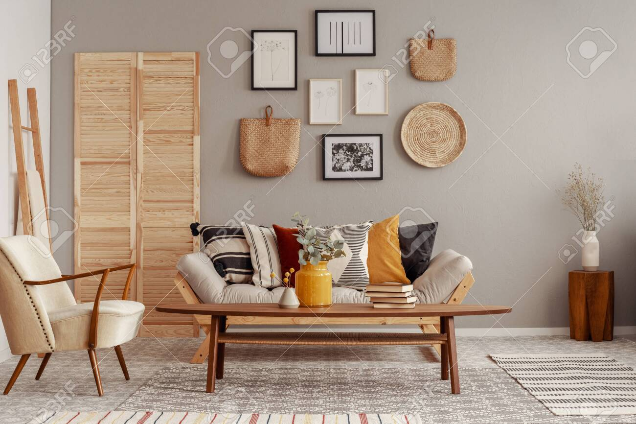 Trendy creme colored armchair in Scandinavian living room interior with gallery of posters on beige wall - 129347479