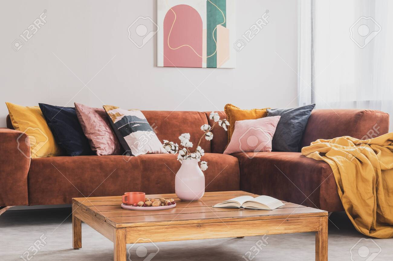 Flowers in vase on wooden coffee table in fashionable living..