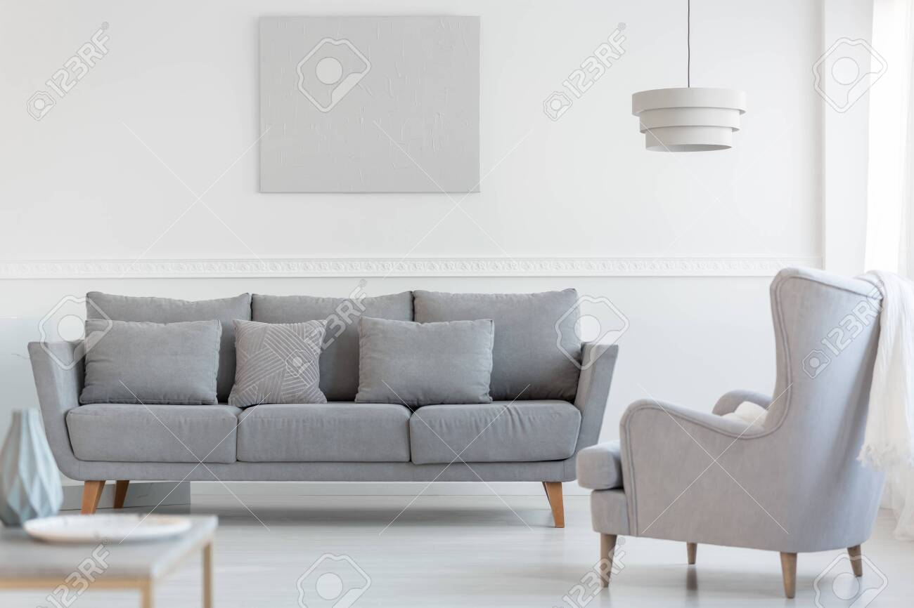 photo big fortable wing back armchair next to long grey scandinavian sofa with pillows in bright living