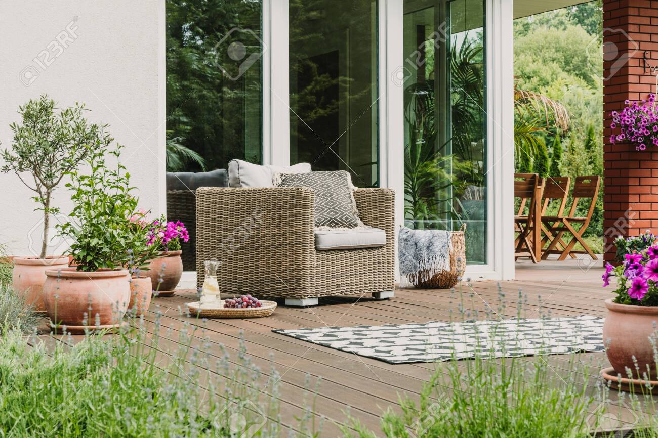 Comfy wicker armchair with pillows on wooden terrace of trendy suburban home - 129348109