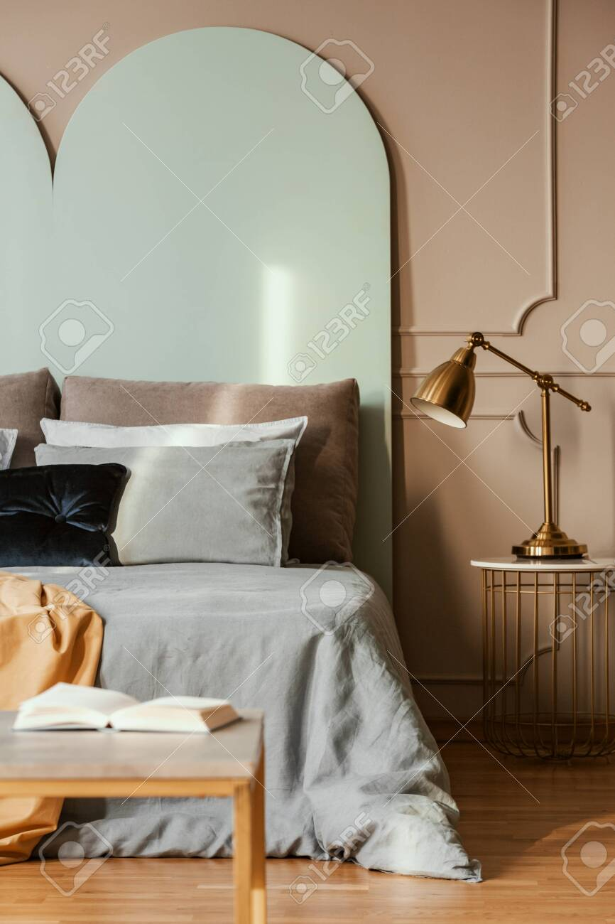 Golden Lamp On Modern Nightstand Table Next To Blue Bed In Grey